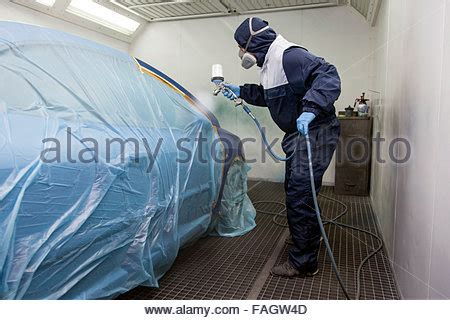 spray painter overalls car spray painter in work overalls with spray paint gun at