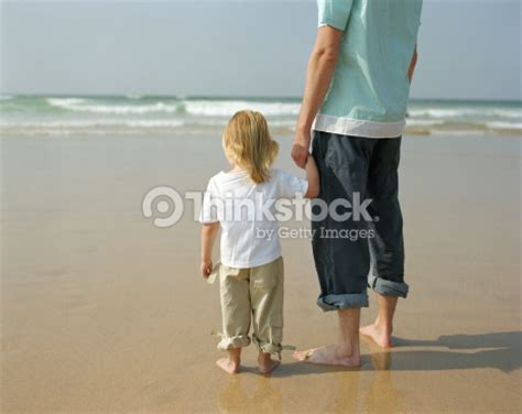 father and daughter holding hands on beach rear view stock