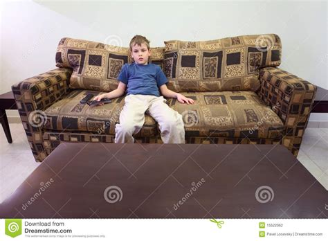 sitting sofa boy with remote control sitting at sofa in room stock