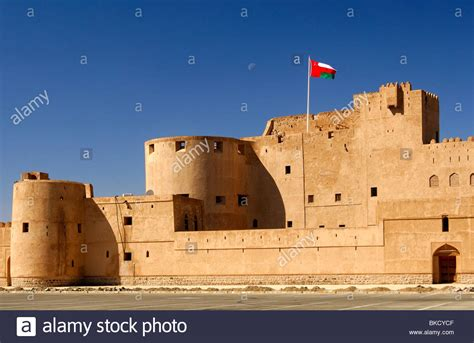 adobe ft national flag of oman fluttering over the jabrin castle historic stock photo royalty free