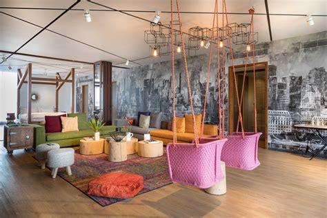 letti appesi al soffitto colorful studio apartment with city skyline wallpaper in