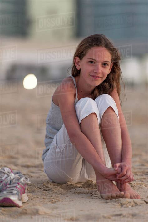 preteen pics preteen girl sitting on beach with barefeet hugging knees