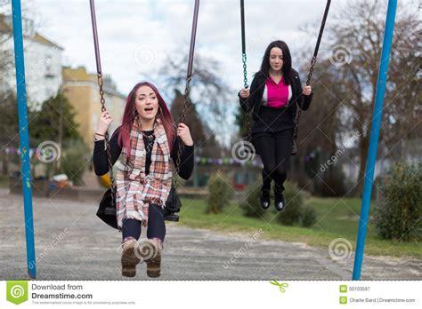 swinging people two teenage girls swinging on swings stock image image