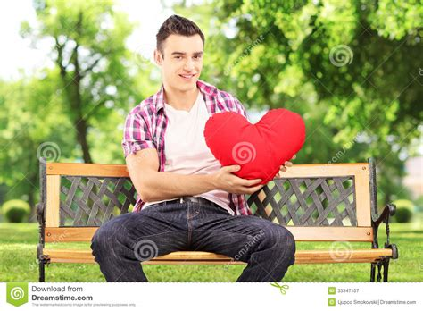 guy sitting on bench smiling guy sitting on a bench and holding a red heart in