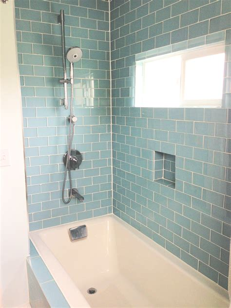 White rectangle bath up with grey accent subway tiles wall panels with built in basket bath