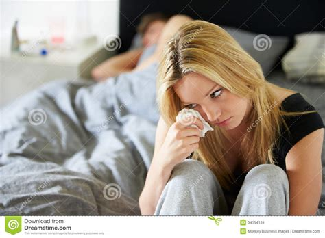 crying at home on the bedroom floor sad teenage girl sitting in bedroom whilst boyfriend
