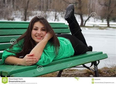girls bench beautiful girl lying on a bench and smiling stock photo