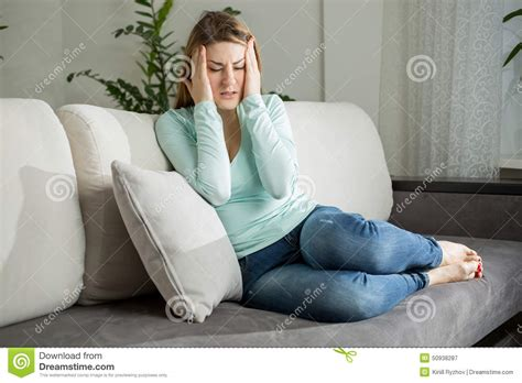handson sofa tired woman lying on sofa and holding hands on head stock