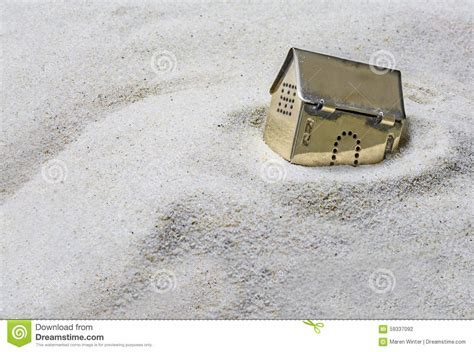 Beach House Plans Free small golden model house sinking into the sand concept of