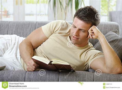 lying on sofa smiling man lying on sofa reading stock image image