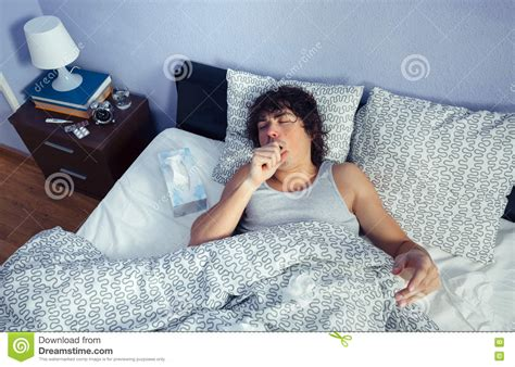 coughing in bedroom only portrait of sick man coughing lying on bed stock photo