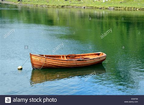 small wooden boat a small clinker built wooden rowing boat tied to a mooring