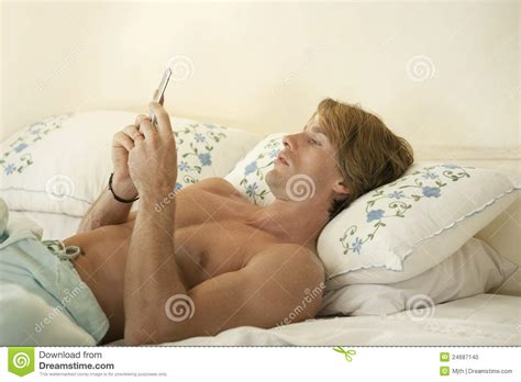 laying down in bed businessman s profile in bedroom texting stock photo