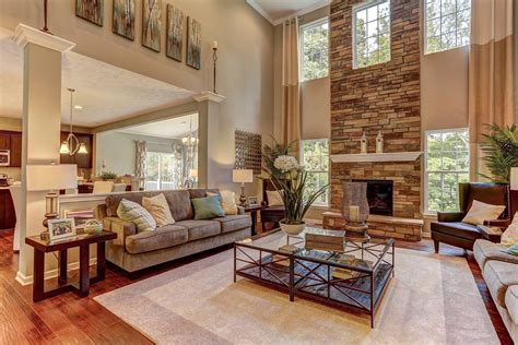 2 story great room windows flank a soaring fireplace in this two story