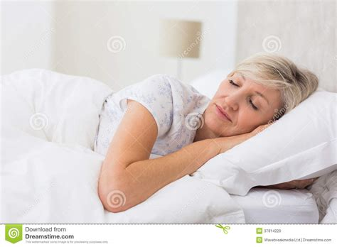 granny bed woman sleeping with eyes closed in bed stock photo image