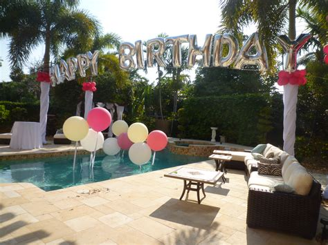 backyard party setup birthday balloon arch over a swimming pool backyard party