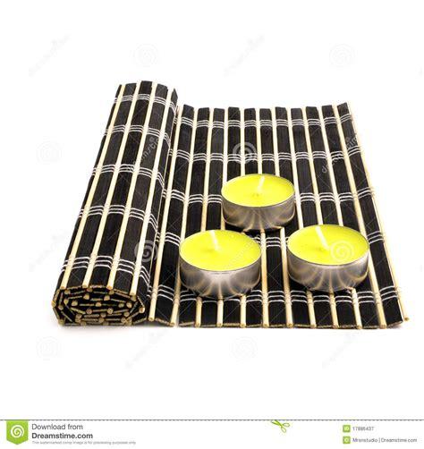 Black Bamboo Mat by Black Bamboo Mat And Three Yellow Candles Royalty Free