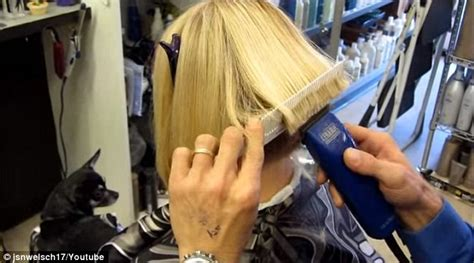 woman cuts hair with fork and clippers hairdresser at m m friseure salon pulls woman s locks into