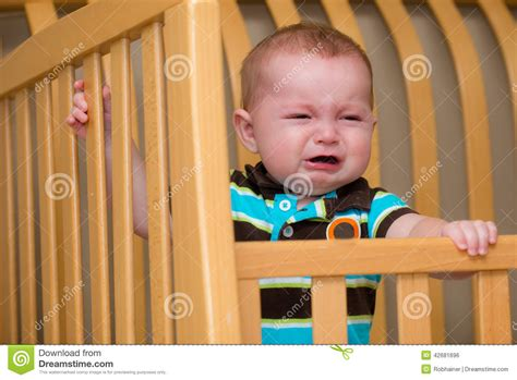 Baby Cries In Crib Unhappy Baby Standing In Crib Stock Photo Image