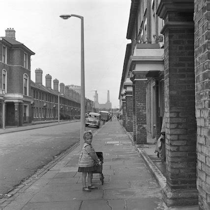 girl playing with pram in street. c.1955 by frederick