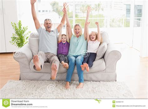 family sofa family of four with arms raised sitting on sofa stock
