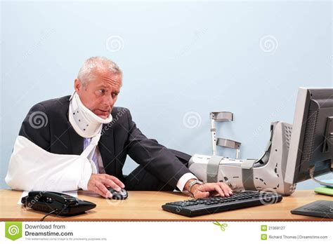 Desk Worker by Injured Businessman Working At His Desk Royalty Free Stock