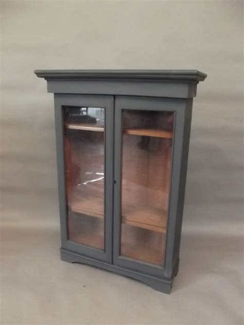 a small painted pine display cabinet with two glazed doors