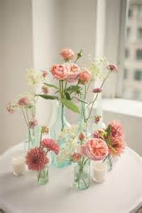 flower centerpieces pink floral arrangements in glass bottles photo by mgb