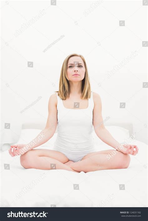 lotus position in bed young woman sitting in lotus position on bed at home stock