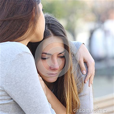 comforting crying girlfriend sad girl crying and a friend comforting her stock photo