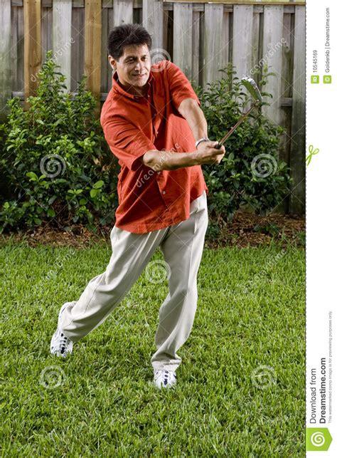 practicing golf swing hispanic man practice golf swing royalty free stock images