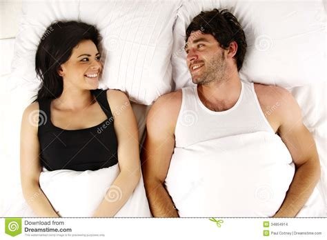 men in bed with other men man and woman laid in bed smiling to each other stock images image 34854914