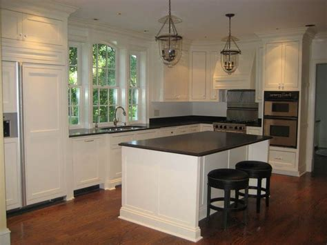 black kitchen island with seating white cabinets with chunky crown moulding and huge window