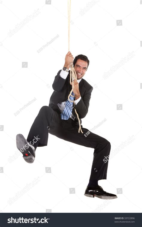 swinging man businessman swinging on a rope isolated over white stock