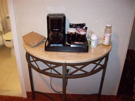 table stand just outside of bathroom coffee maker tea