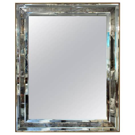 large wall hanging mirror framed with antiqued mirror at