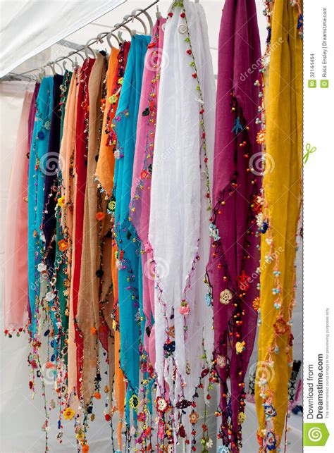 colorful beaded scarves hang in vendor booth at festival