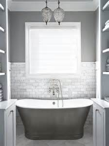 Gray bathroom with gray wall color and marble tiled half wall