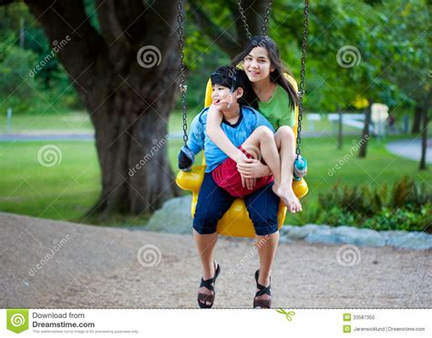swing tv play boy big sister holding disabled brother on special needs swing