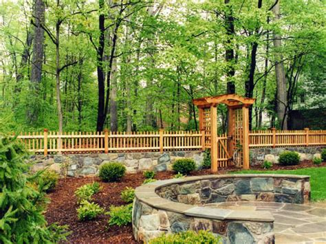 cedar arbor and fence with stone wall rustic landscape