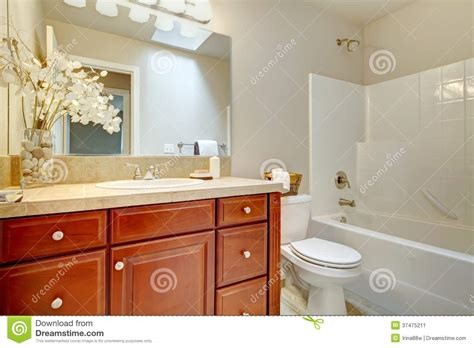 beautiful bright bathroom with cherry wood cabinets stock