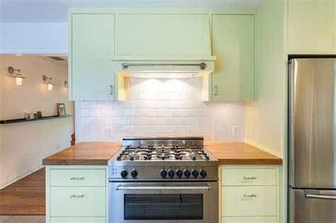 white symmetrical kitchen range with natural wooden white oak wood countertop photo gallery by devos custom