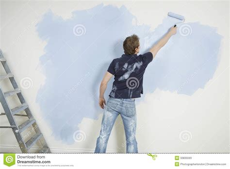 looking for a man who paints houses man painting wall with paintroller stock photos image