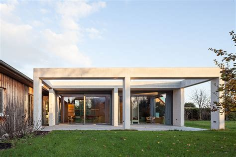 Modern Living Room Idea glass and concrete pavilion extends timber paneled home in