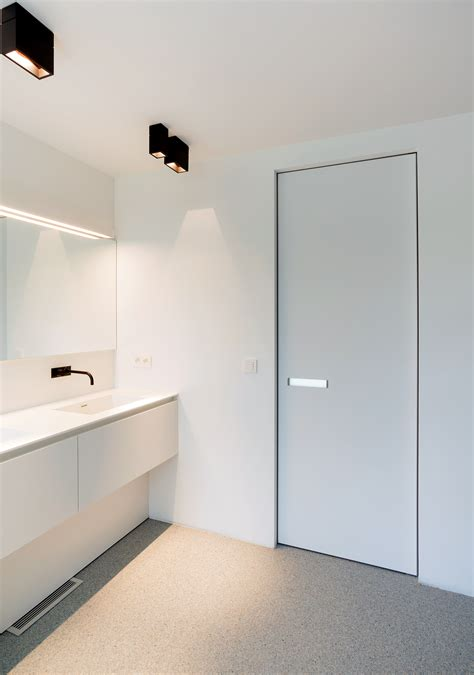white interior door with invisible door frame and a built in plexiglass door handle this modern