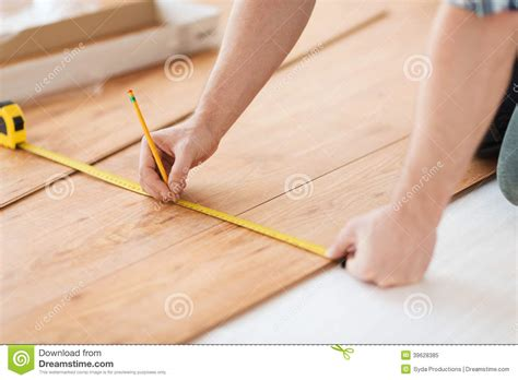 close up of male hands measuring wood flooring stock photo