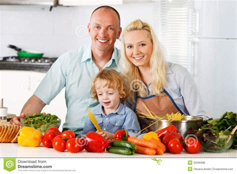 Happy In The Kitchen A Dinner A Signing by Happy Family Preparing A Healthy Dinner At Home Stock