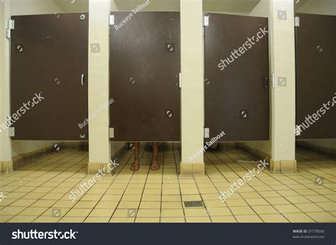 feet under bathroom stall feet showing under bathroom door public stock photo