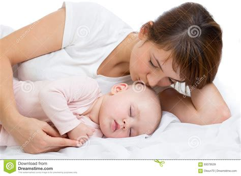 boy kissing a girl in bedroom woman and newborn boy relax in a white bedroom young