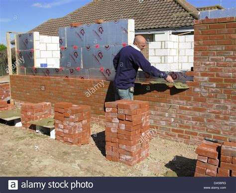 builder cementing building a brick wall with celotex